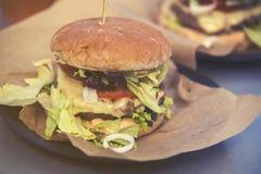 关闭在纸,葡萄酒作用的快餐不健康的汉堡 免版税库存图片