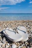 关闭在美丽的希腊海滩的凉鞋 库存图片
