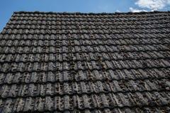 关闭在老房子的年迈的瓦在村庄 在小屋铺磁砖的屋顶的很多青苔  蓝色乡下空的路场面天空 库存照片