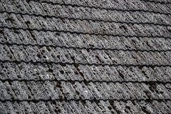 关闭在老房子的年迈的瓦在村庄 在小屋铺磁砖的屋顶的很多青苔  蓝色乡下空的路场面天空 免版税库存图片