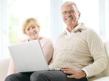 关闭在膝上型计算机前面的一对微笑的资深愉快的夫妇 库存图片