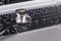 关闭在膝上型计算机的一个听诊器圆盘 免版税库存照片
