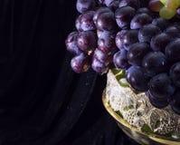 关闭在花瓶的葡萄在黑色 图库摄影