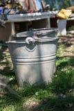 关闭在草的两个生锈的铁桶在庭院里 有垃圾的肮脏的灰色金属桶在仓库广场晴天 图库摄影