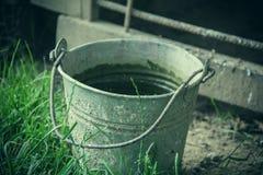关闭在草的生锈的铁桶在庭院里 有垃圾的肮脏的灰色金属桶在仓库广场晴天 库存图片
