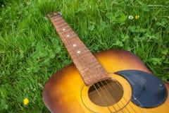 关闭在草的老木声学吉他 图库摄影