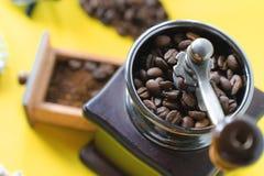 关闭在葡萄酒木磨咖啡器的顶视图有选择性的咖啡豆和碾碎的咖啡豆在黄色背景 免版税库存照片