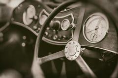 关闭在葡萄酒跑车车的减速火箭的摄影的仪表板和方向盘 图库摄影