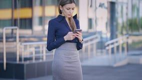 关闭在蓝色女衬衫打扮的美丽的女商人,灰色裙子,并且短剑被停顿的鞋子站立户外 股票录像