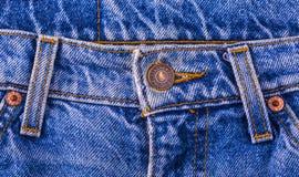 关闭在蓝色牛仔裤的莱维` S按钮 图库摄影