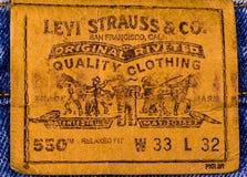 关闭在蓝色牛仔裤的莱维` S皮革标签 免版税库存图片