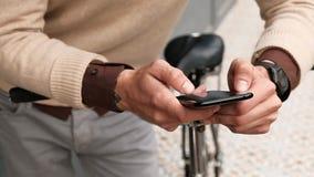 关闭在行家人的手上有单一速度自行车冲浪的互联网的智能手机的 影视素材