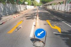 关闭在街道路车道的双向黄色箭头交通标志  免版税库存照片