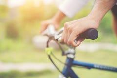 关闭在被弄脏的自然日出backg的骑自行车的人手上 免版税库存照片
