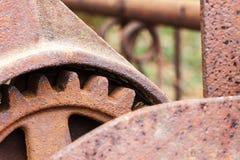关闭在被放弃的农场设备的生锈的齿轮 免版税库存照片