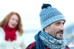 关闭在被编织的帽子的人画象 与妇女的愉快的人画象背景的 人特写镜头焦点和妇女后面的 库存图片