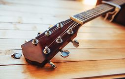 关闭在轻的木背景的脖子音响古典吉他 免版税库存图片