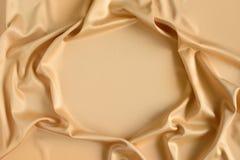 关闭在金子色的丝织物的波纹在框架形状  缎纺织品背景 赠送阅本空间 免版税库存图片