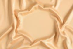 关闭在金子色的丝织物的波纹在框架形状  缎纺织品背景 赠送阅本空间 库存图片
