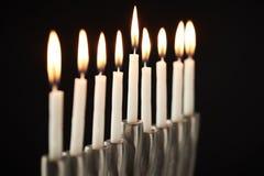 关闭在金属光明节犹太教灯台的升蜡烛反对黑演播室背景 免版税图库摄影