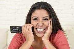 关闭在长沙发愉快激动的画象年轻美丽的西班牙妇女家庭观看的电视 免版税图库摄影