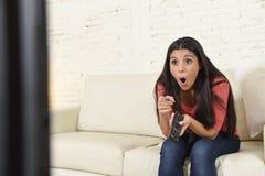 关闭在长沙发愉快激动的画象年轻美丽的西班牙妇女家庭观看的电视 免版税库存图片