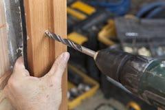 关闭在门框两侧的直木的一个电钻操练的孔 免版税库存图片