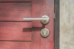 关闭在闭合的棕色木门的门把手 免版税库存照片