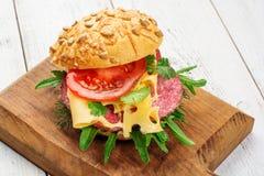 关闭在面包的稀薄地切的辣蒜味咸腊肠鲜美开胃菜用乳酪、蕃茄和草本在一个切板与 免版税库存图片