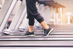 关闭在鞋子,与运行在踏车的腿的妇女训练并且烧在身体的油脂在健身房、健康生活方式和体育 库存照片