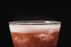 关闭在飞溅在黑ba的玻璃和泡影苏打的冰可乐 免版税库存照片
