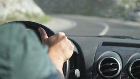 关闭在驾驶在漫长的路的方向盘的男性手一辆汽车沿山 免版税库存照片