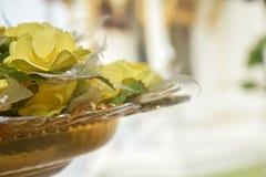 关闭在黄铜碗的黄色花在背景,复制空间 免版税库存照片