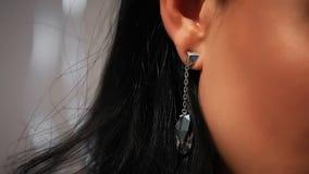 关闭在黑发妇女的耳朵的耳环 库存照片