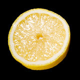 关闭在黑色的一个切的柠檬 库存照片