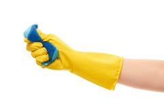 关闭在紧压蓝色清洁海绵的黄色防护橡胶手套的女性手 库存图片