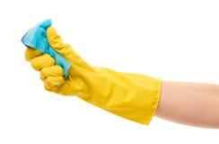 关闭在紧压蓝色清洁海绵的黄色防护橡胶手套的女性手 库存照片