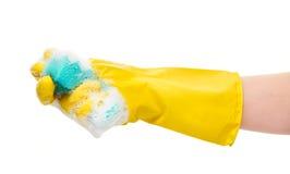 关闭在紧压绿色清洁海绵的黄色防护橡胶手套的女性手在泡沫 图库摄影