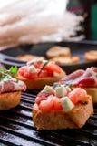 关闭在黑格栅背景的集合bruschetta 鲜美开胃小菜 免版税库存图片