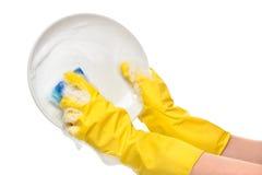 关闭在洗涤有蓝色清洁海绵的黄色防护橡胶手套的女性手白色板材 免版税图库摄影