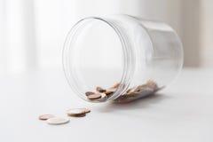 关闭在玻璃瓶子的欧洲硬币在桌上 图库摄影