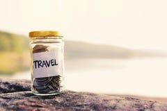 关闭在玻璃瓶子的硬币有旅行词的 库存图片