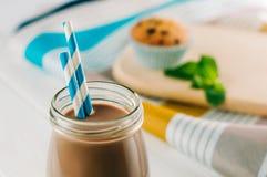 关闭在玻璃瓶的巧克力牛奶有蓝色镶边str的 免版税图库摄影