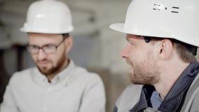 关闭在建筑区域的防护盔甲的两个有胡子的人 工头和工作者站立 股票录像