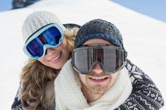 关闭在滑雪风镜的一对夫妇反对雪 免版税库存图片
