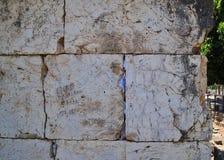 关闭在Capernaum古老废墟的祷告被充塞的玄武岩砖墙  库存图片
