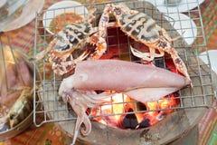 关闭在charcoa烤的新鲜的乌贼和马螃蟹烤肉 库存照片