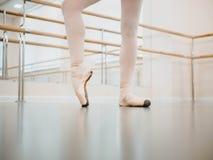 关闭在pointe的腿 在表现前的训练 实践在芭蕾舞短裙礼服的古典芭蕾的妇女在健身房或 免版税库存照片