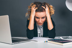 关闭坐在她的书桌的画象年轻女商人在办公室 研究便携式计算机,计划一个新的项目 免版税图库摄影