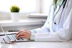 关闭坐在桌上的未知的女性医生在窗口附近在医院 库存图片